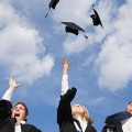 High school graduates throwing their mortarboards in the air --- Image by © Royalty-Free/Corbis